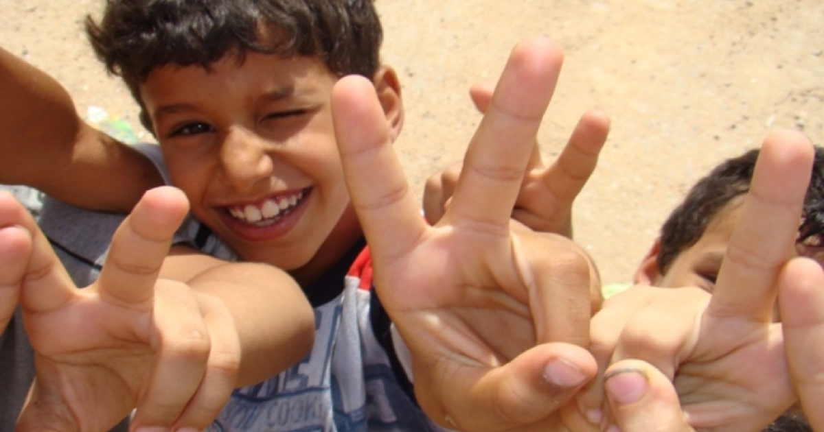 Children from Sirte make the victory sign showing support for the rebels as their families wait for clearance at the Estada checkpoint after fleeing from Sirte Monday.</p>