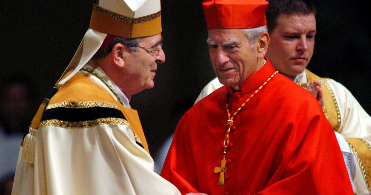 Newly installed Archbishop of Philadelphia Justin Rigali (L) is greeted by Cardinal Anthony Bevilacqua, Archbishop Emeritus of Philadelphia, during the installation ceremony October 7, 2003 in Philadelphia, Pennsylvania.</p>
