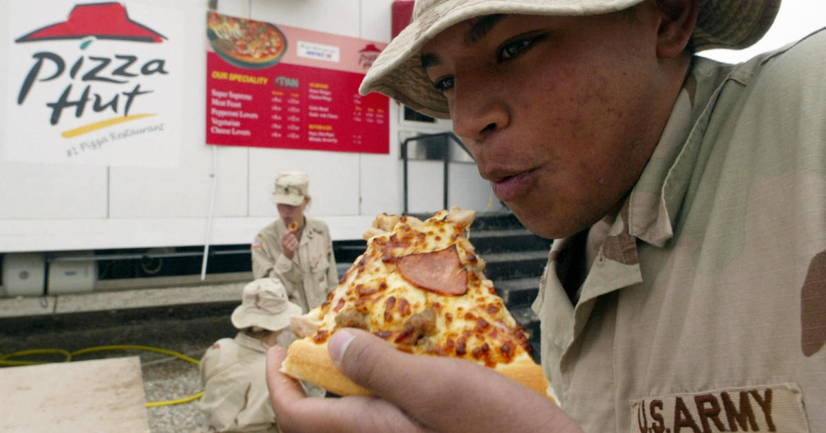 A US soldier eats pizza at the military base of Talil, near Nasiriyah in southern Iraq.</p>