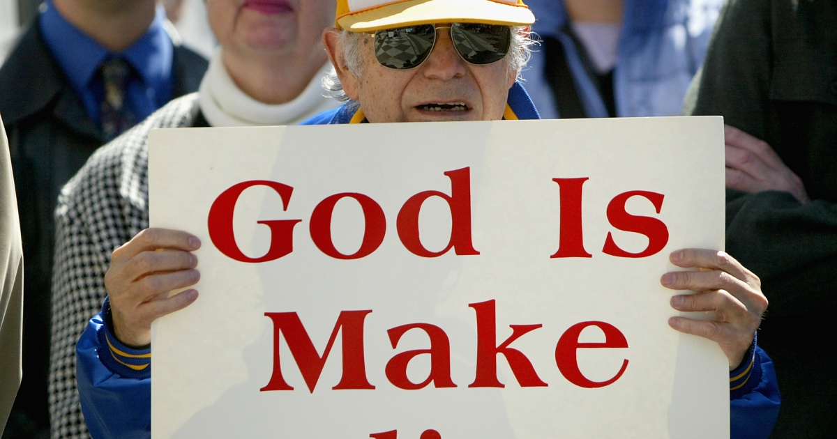 A member of the American Athiests in favor of removing the phrase 'under god' from the Pledge of Allegiance holds up a sign during a protest March 24, 2004 outside of the Ninth Circuit Court of Appeals in San Francisco.</p>