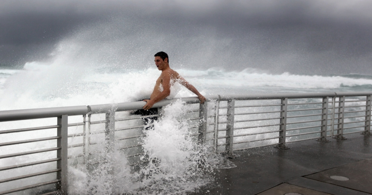 Cory Ritz braces himself as a wave bursts onto a pier at the Boynton Beach inlet on August 25, 2011 in Boynton Beach, Florida.</p>