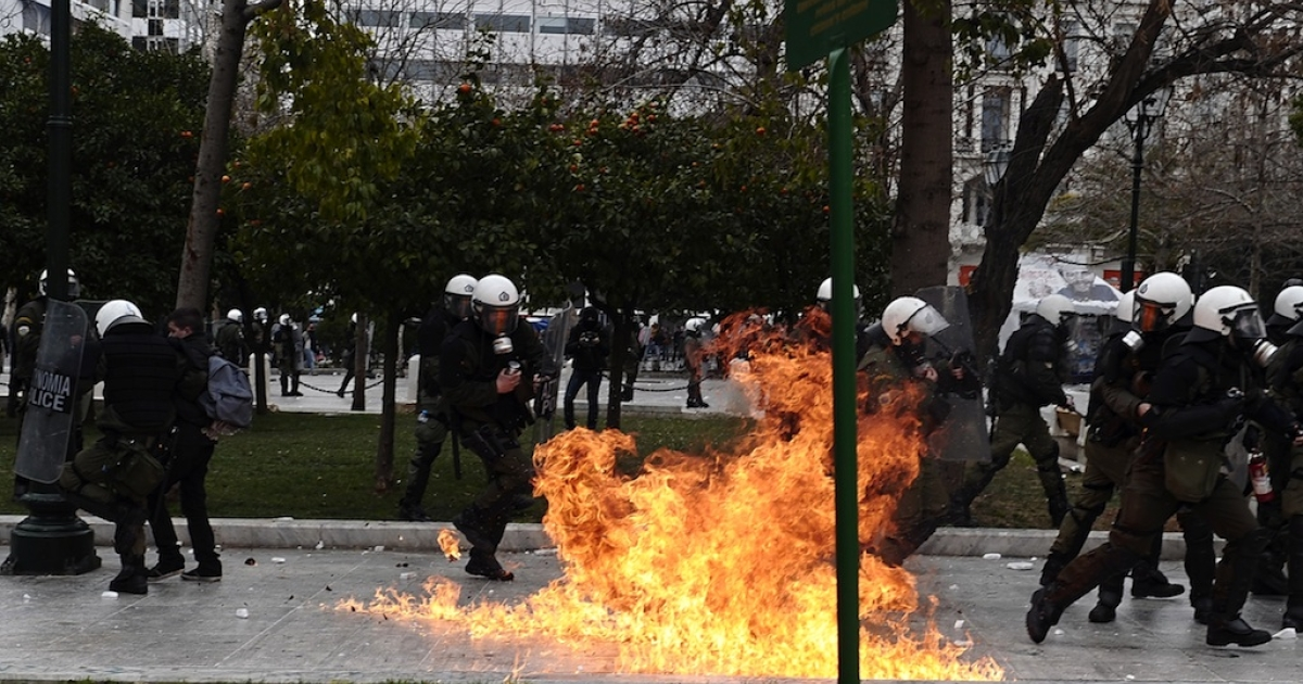 Riot police dodge a firebomb in Athens on Feb. 10.</p>