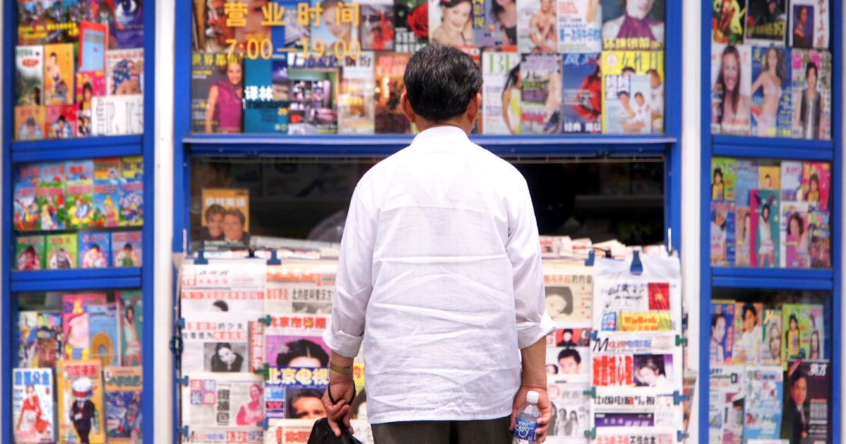 A man appears overwhelmed with the choices of magazines and newspapers for sale 25 May 2000 at a street-side news stand in Beijing, China.</p>