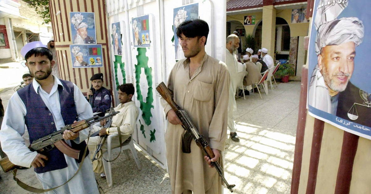 Armed Afghan security guards stand alert outside the campaign office of Afghan President Hamid Karzai in Peshawar, 27 September 2004.</p>
