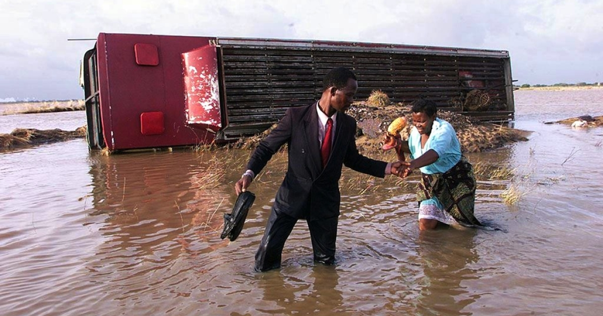 A Mozambican man helps his wife cross the flooded highway to Xai-Xai from Maputo, Feb. 22, 2000. At least 700 people died, and a million were displaced, after the tropical storm 12 years ago that caused the worst floods in Mozambique's history. On Jan. 19, 2012, emergency officials in Mozambique said five people had died after Tropical Storm Dando hit the coast, causing flooding in Maputo and Gaza province.</p>