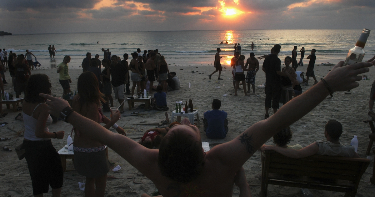 Revelers continue to dance as the sun rises over Sunrise Beach in Haadrian, Koh Phangan.</p>