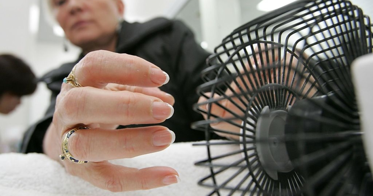 SAN FRANCISCO - MARCH 03: Linda Donly-Reid, a customer at JT Nails, uses a small fan to dry her nails after receiving a manicure March 3, 2006 in San Francisco. California Assembly Speaker pro Tem Leland Yee (D-San Francisco) has renewed calls to pass new legislation to clean up unsanitary nail salons after a woman in Fort Worth, Texas died as a result of a staph infection caused by bacteria from a nail salon.</p>
