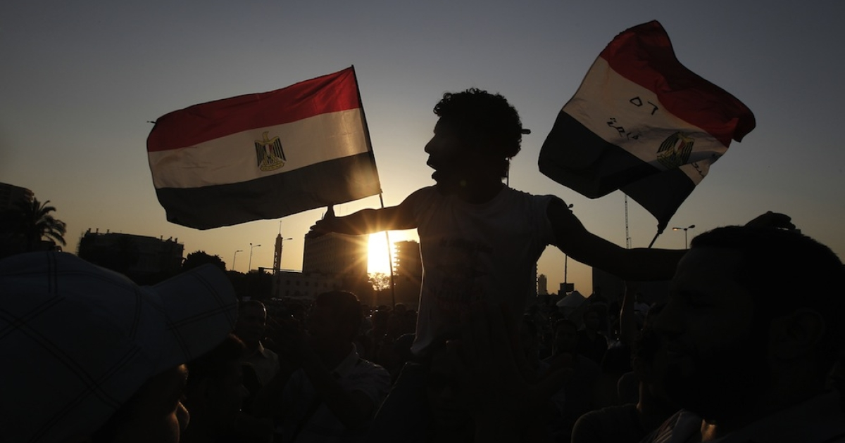 Egyptian protesters wave their national flags in Cairo's Tahrir Square. Over the past year there has been little movement on human rights issues such as religious tolerance and women's rights.</p>