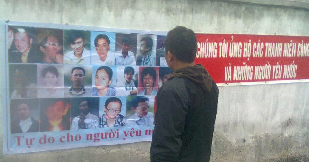 A man looks at a banner representing the 14 activists convicted on January 9th in Vinh City, Vietnam. Source: thanhnienconggiao.blogspot.com</p>