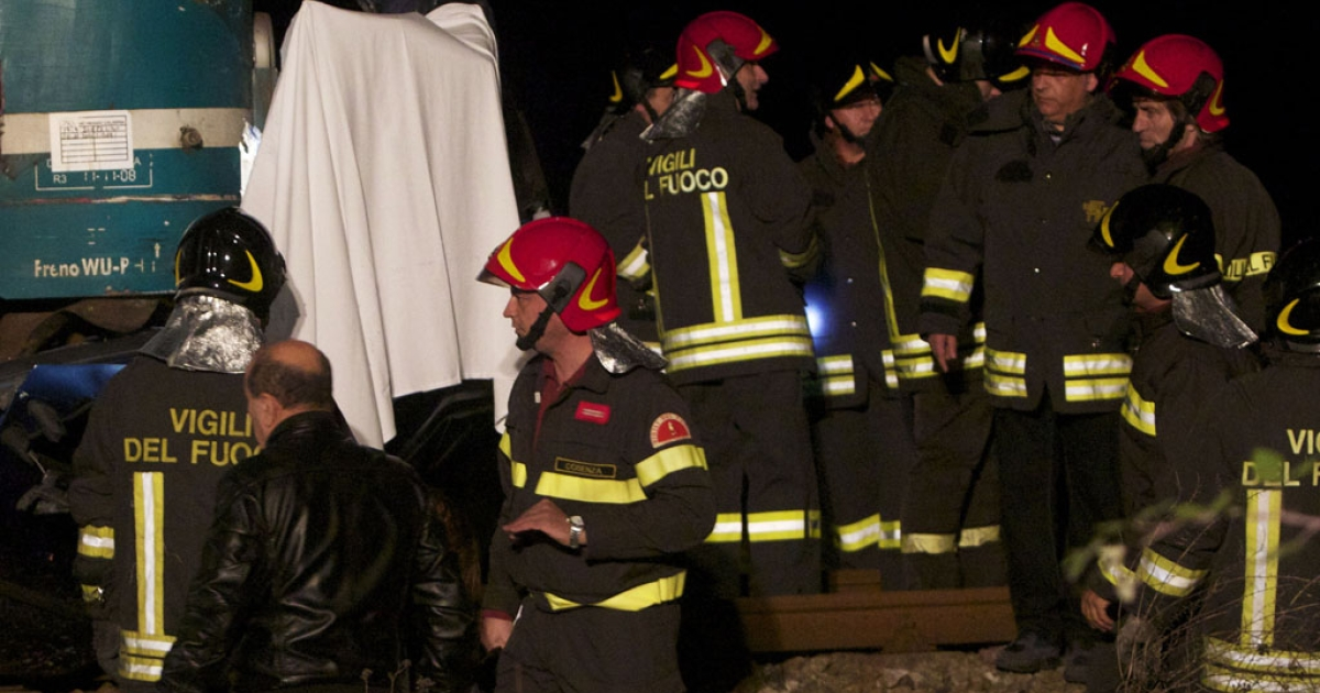 Italian firefighters work at the site where a train collided with a van full of Romanian workers in Rossano on November 24, 2012. Six Romanian workers who were involved in the seasonal picking of clementines were killed when the train struck their car at a crossing.</p>
