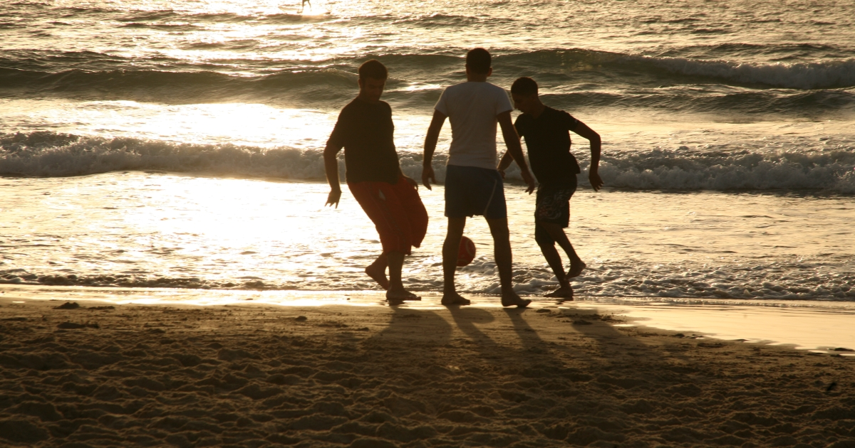 Young men play soccer on the beach of Tel Aviv while surfers ride the waves behind them. Tel Aviv is noted for its relaxed lifestyle, often seemingly a haven far removed from the conflicts within Jerusalem and other cities in the region.</p>