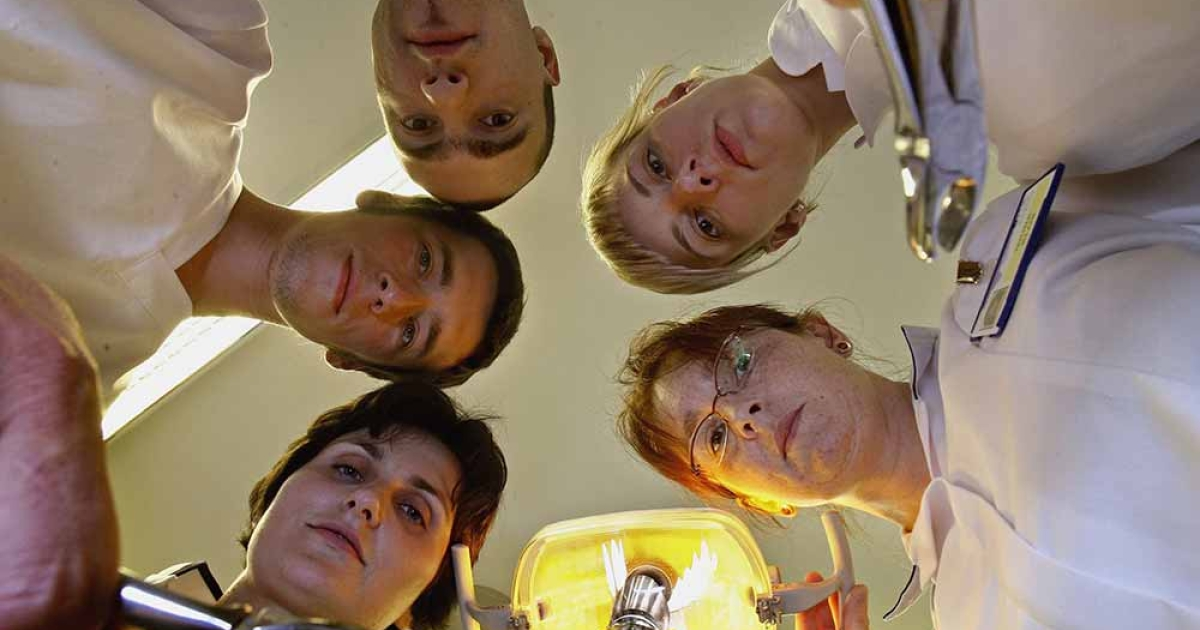 Polish salaried dentists gather round a surgery chair at Lochmaben hospital June 12, 2006, Lochmaben in Scotland.</p>