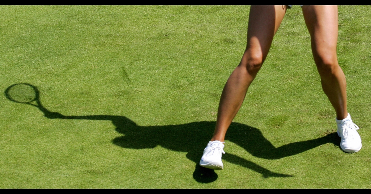 The shadow of Russian tennis player Maria Sharapova falls on a grass court at Wimbledon, in south London, 23 June 2006.</p>