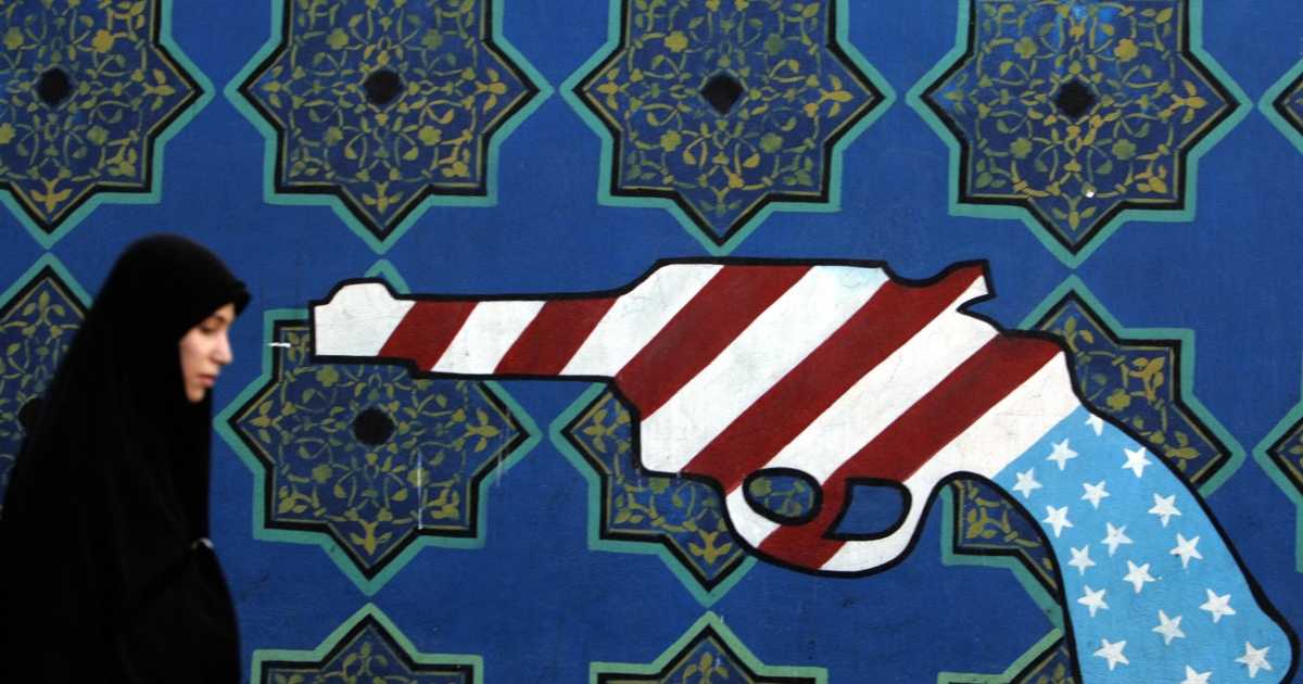 An Iranian woman walks past a mural painting of a revolver on the walls of the former US embassy in Tehran during a protest marking the 27th anniversary of the seizure of the US diplomatic mission by Islamist students.</p>