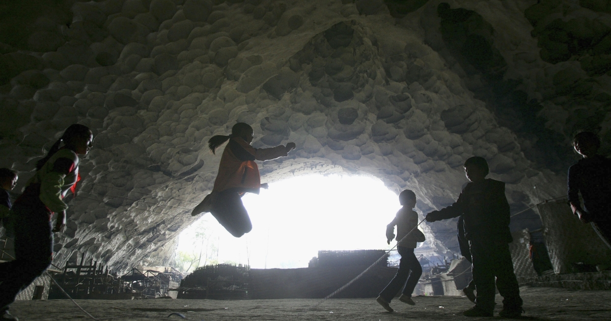 Chinese children play rope-skipping at the playground of a school in a huge cave at a remote Miao village on March 16, 2007 in Ziyun county, Guizhou province of southwest China.</p>