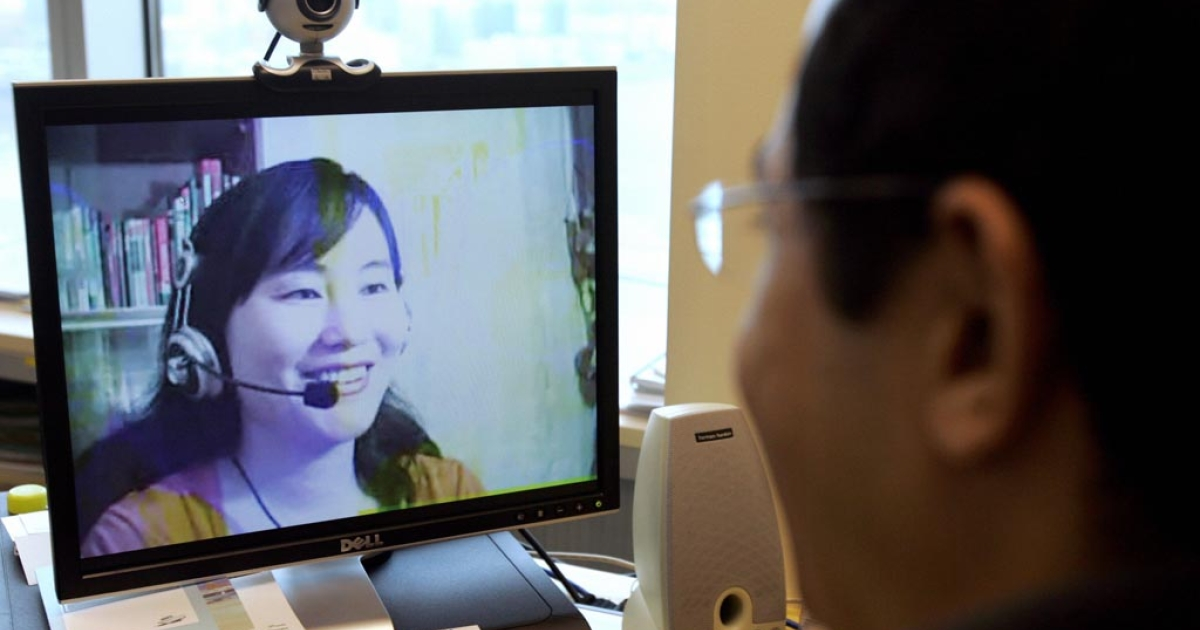 A computer user in Hong Kong, looking at an image of online Mandarin teacher Lily Huang at her home on mainland China.</p>