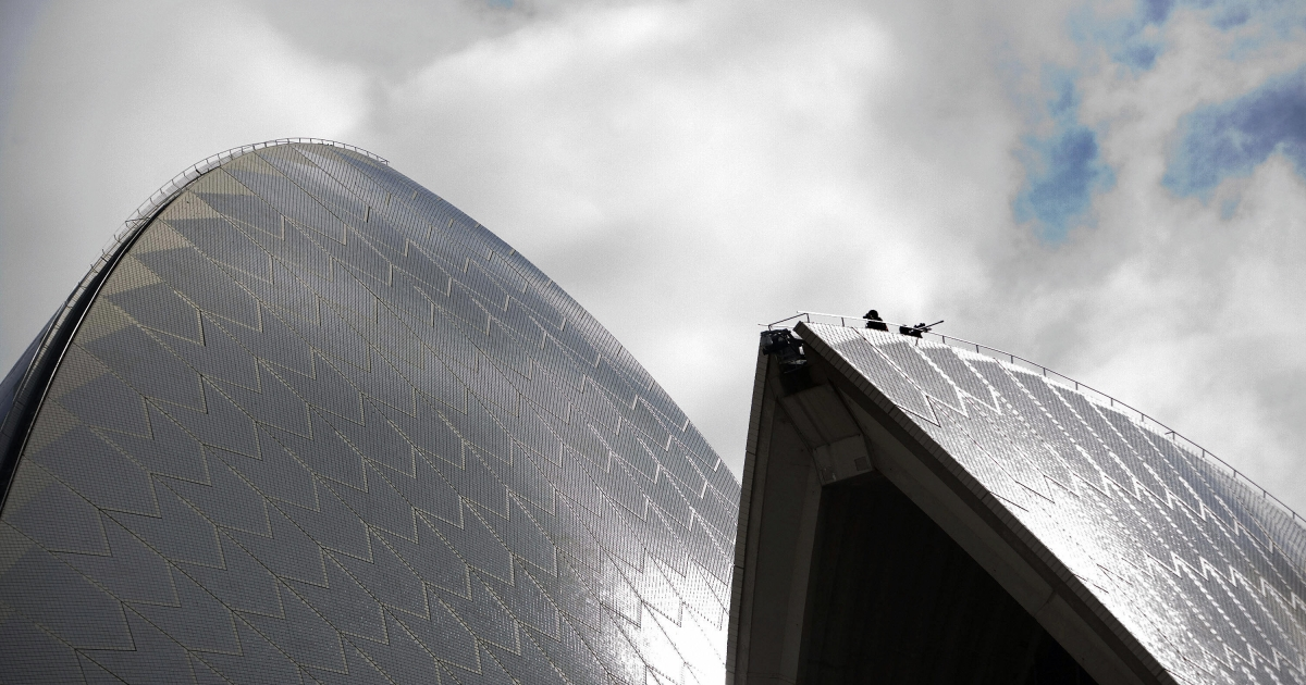 A US Secret Service spotter and sniper (R) sits atop the Sydney Opera House during the visit of US President George W. Bush arrives to speak during the Asia-Pacific Economic Cooperation Summit in 2007.</p>