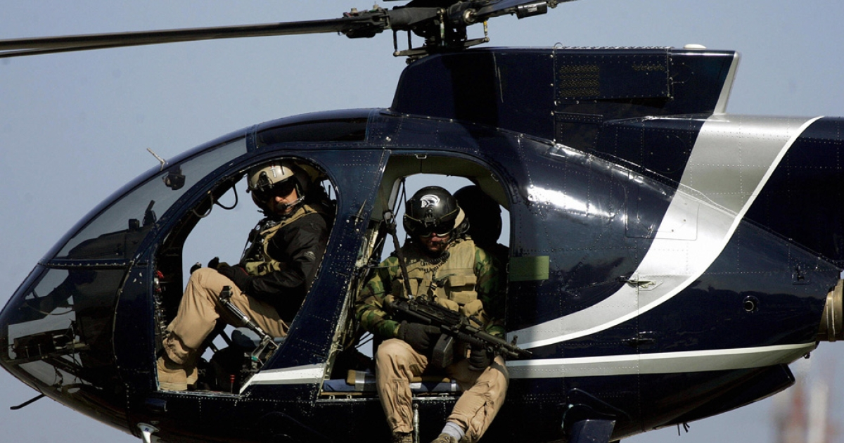 In a file picture dated  February 5 2005, members of the US-based Blackwater private security firm scan Baghdad from their helicopter. Blackwater was back on the streets of Baghdad four days after being grounded following a shooting incident in which 10 people were killed, a US official said.</p>