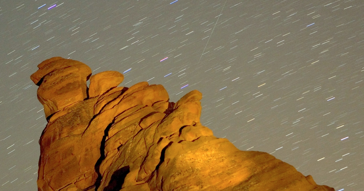 A Geminid meteor streaks diagonally across the sky against a field of star trails over one of the peaks of the Seven Sisters rock formation in this exposure early December 14, 2007 in the Valley of Fire State Park in Nevada.</p>