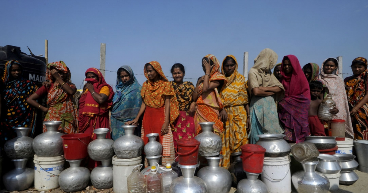 Bangladeshi women queue up with containers to receive water in Dhaka. The capital needs 2.2 billion litres of water a day, but the city's water authorities can supply just 1.9 billion litres, according to official figures.</p>