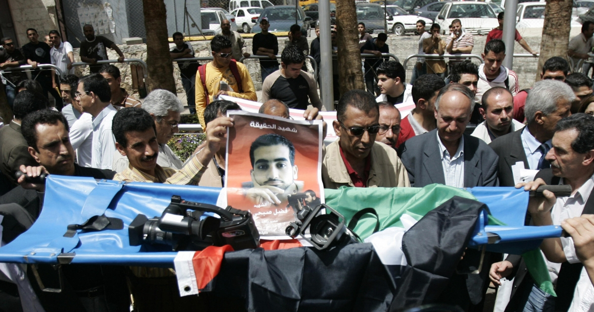 Palestinian journalists hold a stretcher carrying a camera and bearing a portrait of Reuters cameraman Fadel Shana during protest in the West Bank city of Ramallah against his killing in the Gaza Strip on April, 20, 2008. The International Press Institute, a media watchdog, condemned the killing.</p>