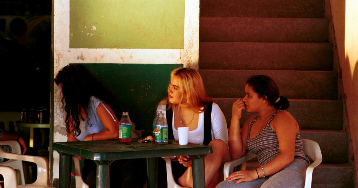 Prostitutes sit at an outdoor table February 21, 2001 in Peas Coloradas, Colombia.</p>