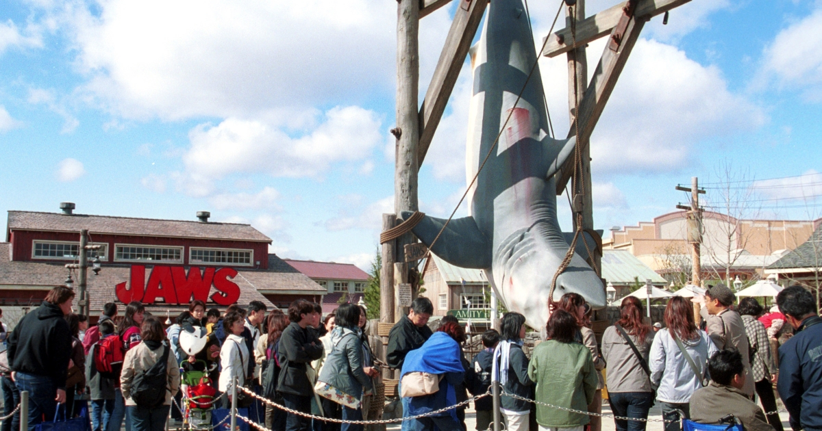 Visitors crowd around a hanging shark display near the ride, themed after the Steven Spielberg motion picture