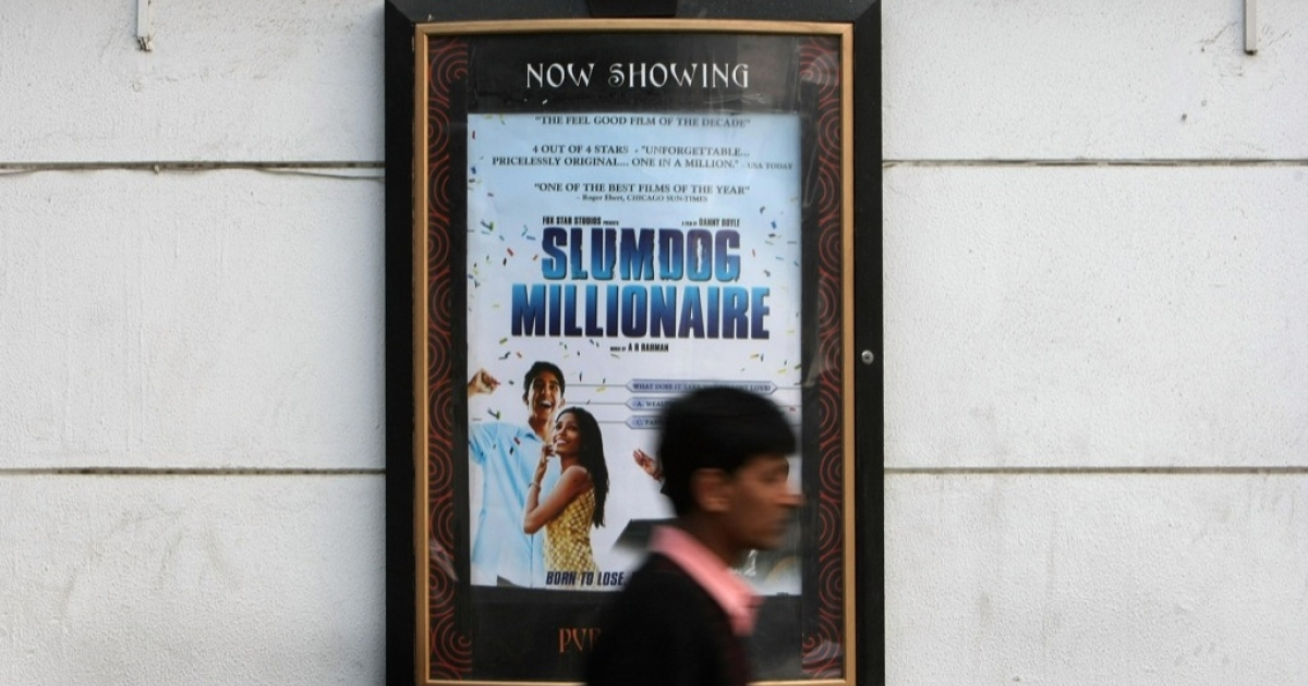 An Indian man walks past a poster of the Oscar nominated film 'Slumdog Millionaire' in New Delhi on January 23, 2008.</p>