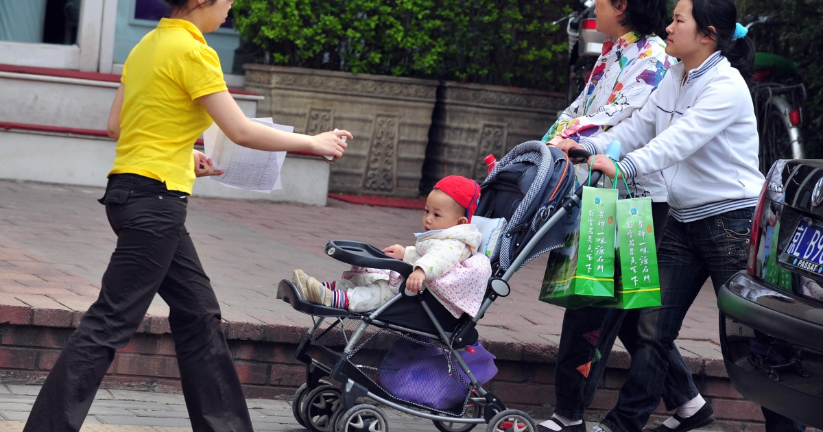 A woman pushes a baby boy riding in a pram along a Beijing street on April 10, 2009. Selective abortion in favour of males has left China with 32 million more boys than girls, creating an imbalance that will endure for decades, an investigation released on April 10 warned.</p>