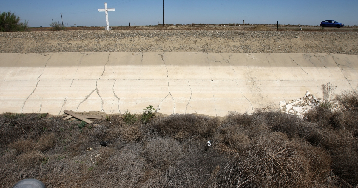 A dried-up irrigation canal filled with tumbleweeds in Central Valley, California.</p>