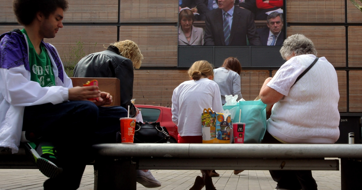 People eat their lunch on benches in the town centre of Swindon, England.</p>