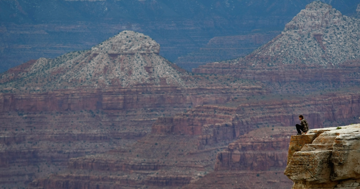 A tourist sits on a precipice while gazing out into the Grand Canyon June 10, 2009 at sunset in the Grand Canyon National Park, Arizona.</p>