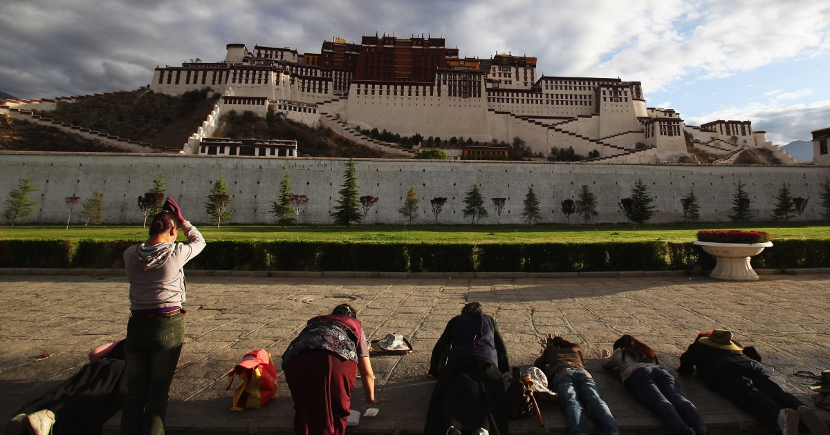 Tibetan pilgrims prostrate themselves in front of the Potala Palace on June 21, 2009 in Lhasa, Tibet Autonomous Region, China.</p>