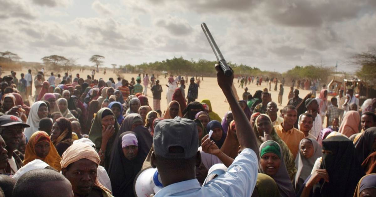 A security officer keeps order for hundreds of people desperate to move to a less crowded refugee camp in Dadaab, the world's biggest refugee complex August 20, 2009 in Dadaab, Kenya.</p>