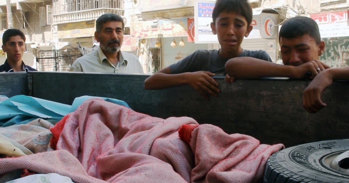 Two young Syrian boys cry as they look over the covered bodies of eight cousins killed by an airstrike in Aleppo, Syria. A separate attack in the northern village of Ain Issa on Sept. 20, 2012 killed and wounded dozens of civilians.</p>