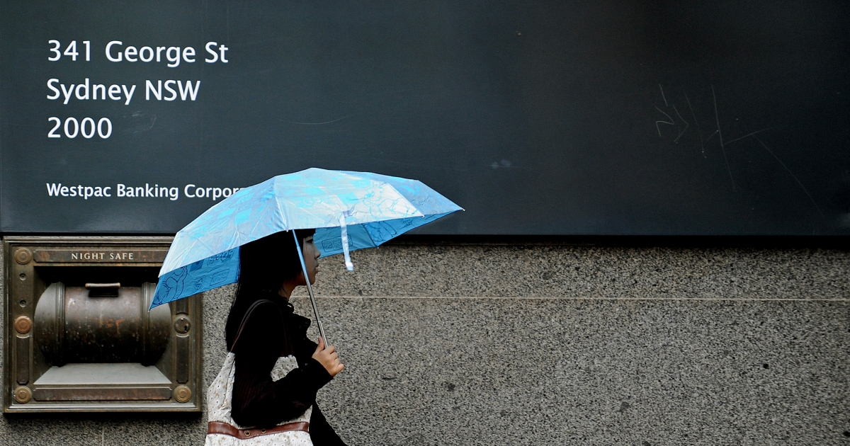A woman shelters under an umbrella as she walks past a Westpac Banking Corporation branch in central Sydney on October 26, 2009.</p>