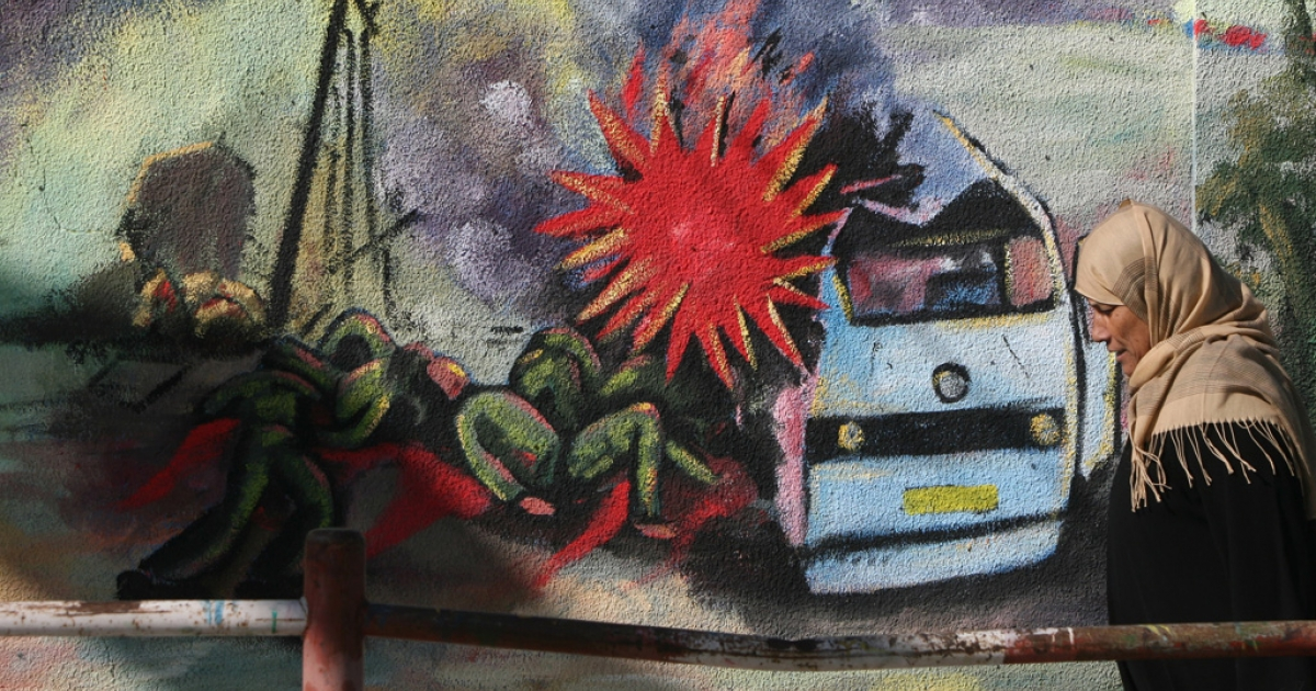 A Palestinian school woman walks past part of a mural painted by a Hamas artist, representing the bombing of a bus in Israel, on December 13, 2009 in the northern Gaza Strip refugee camp of Jabalia.</p>