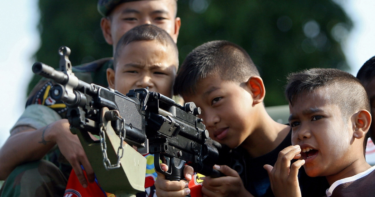 Thai children aim an armored vehicle-mounted rifle as a soldier watches during a gathering at a Navy camp on the occasion of National Children's Day in Thailand's restive southern province of Narathiwat on January 9, 2010.</p>