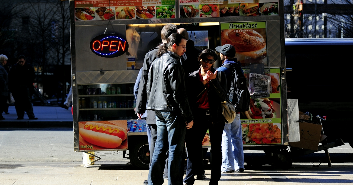 People wait in line to buy thier lunch at a street food vendor cart in New York, March 8, 2010.</p>