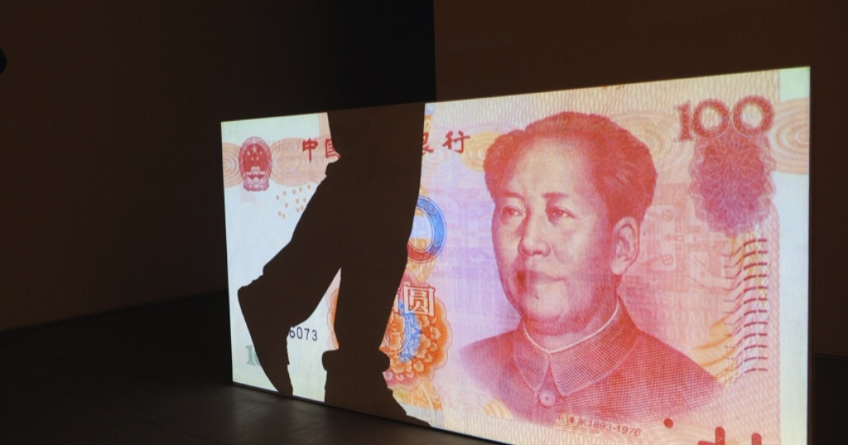 The shadow of a visitor falls on a huge 100 Yuan note on display at an art exhibiton in 798 art factory in Beijing on April 15, 2010.</p>