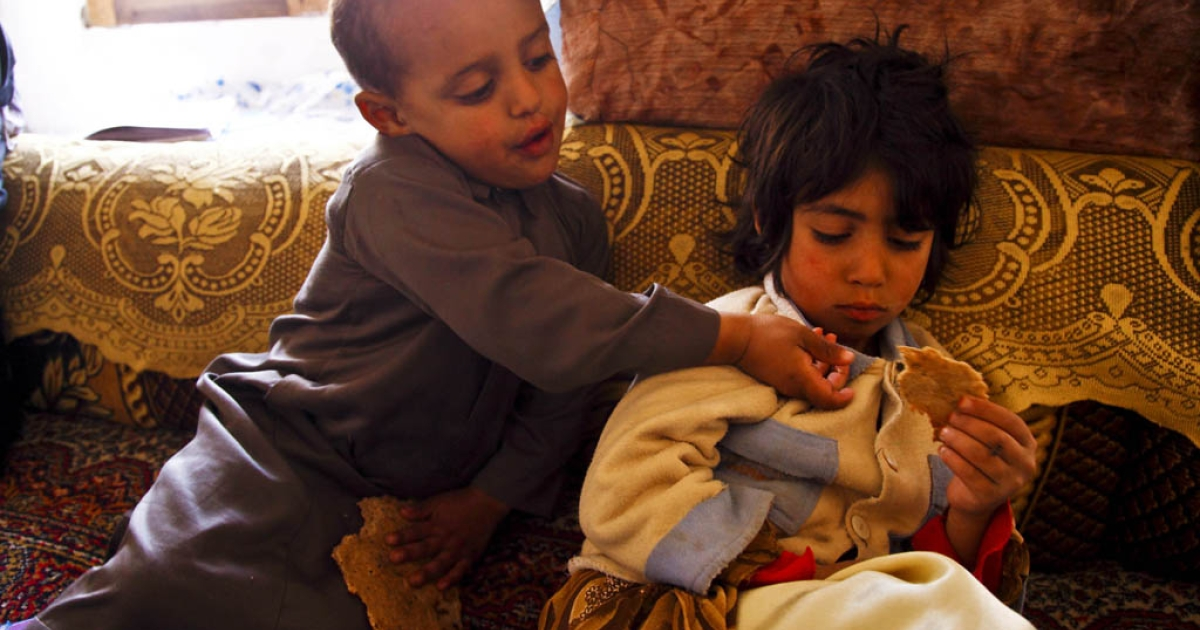 Two Yemeni children share a piece of bread. Since the political crisis came to the boil at the beginning of the year, food prices have soared leaving many families struggling to feed their children this Ramadan, the Muslim holy month of fasting.</p>