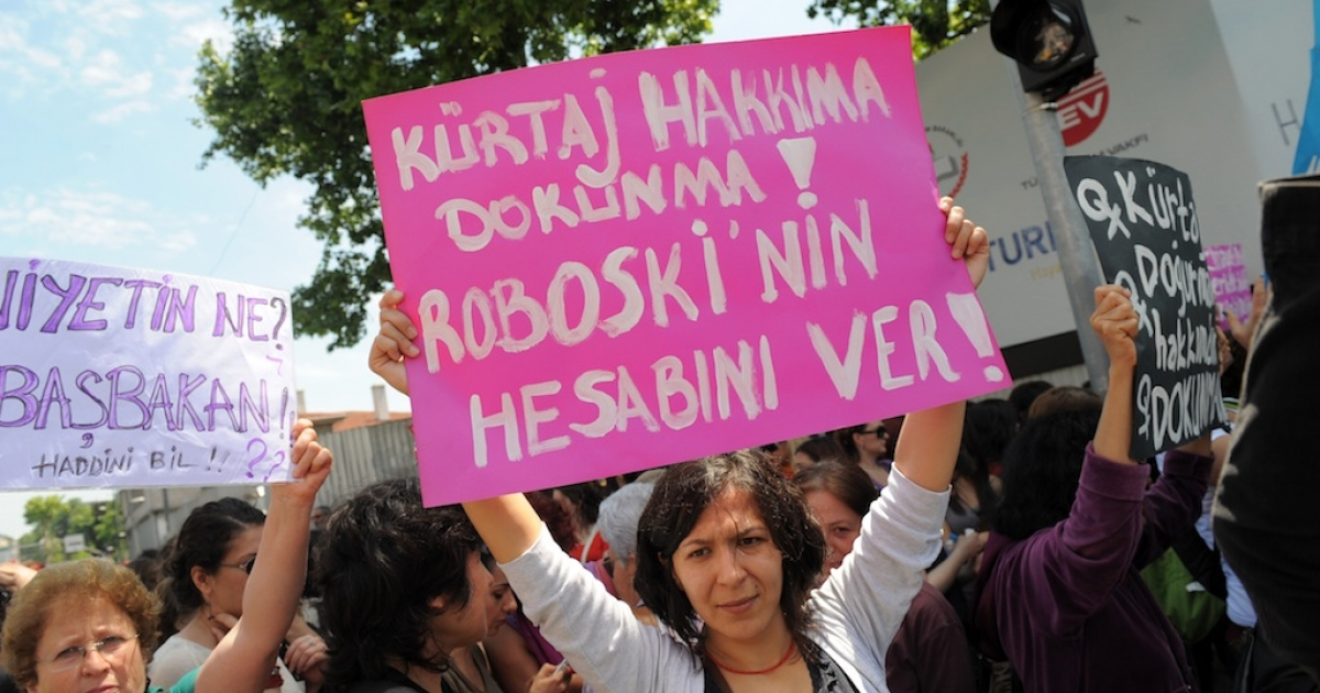 A Turkish feminist (R) holds a placard reading 'Don't touch our abortion rights' during a protest outside Turkish Prime Minister's office in Istanbul in May, 2012. In Turkey, abortion is technically legal during the first 10 weeks of pregnancy, but women have recently reported significant roadblocks to safe procedures.</p>