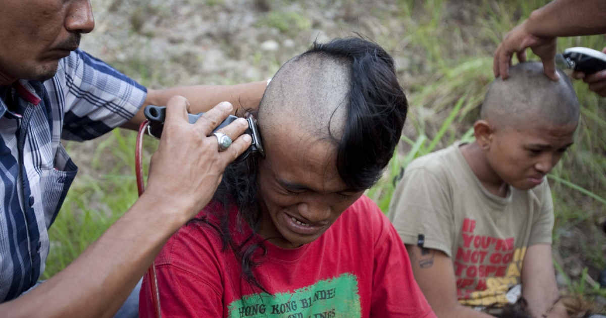 Police shave the mohawk of a detained Indonesian punk at a police school in Aceh Besar in Aceh province, Indonesia, Dec. 13, 2011.</p>