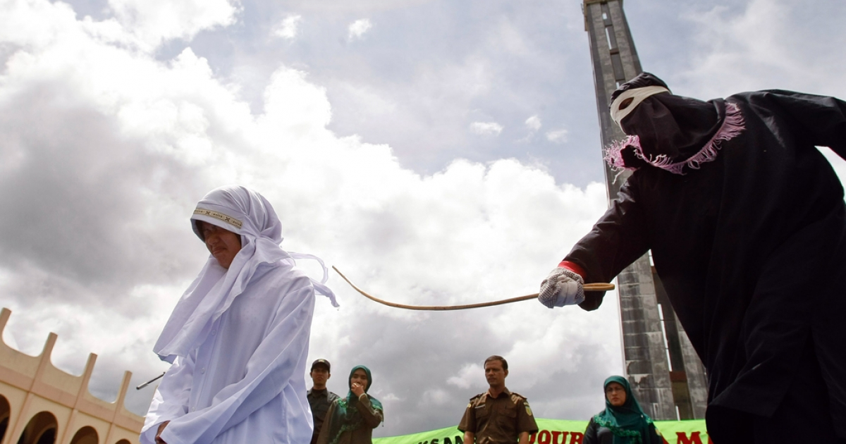A masked person canes Indonesian food seller Murni Amris for violating Islamic Shariah law outside a mosque in Jantho, Aceh province, Oct. 1, 2010.</p>