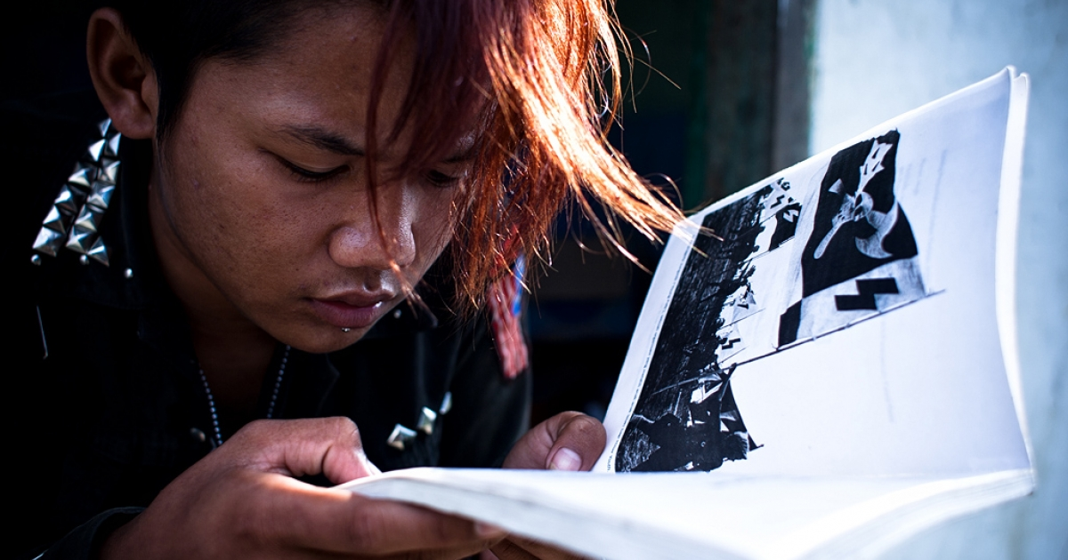 A punk member reads a book about history of Punk, Banda Aceh, Aceh Province, Indonesia.</p>