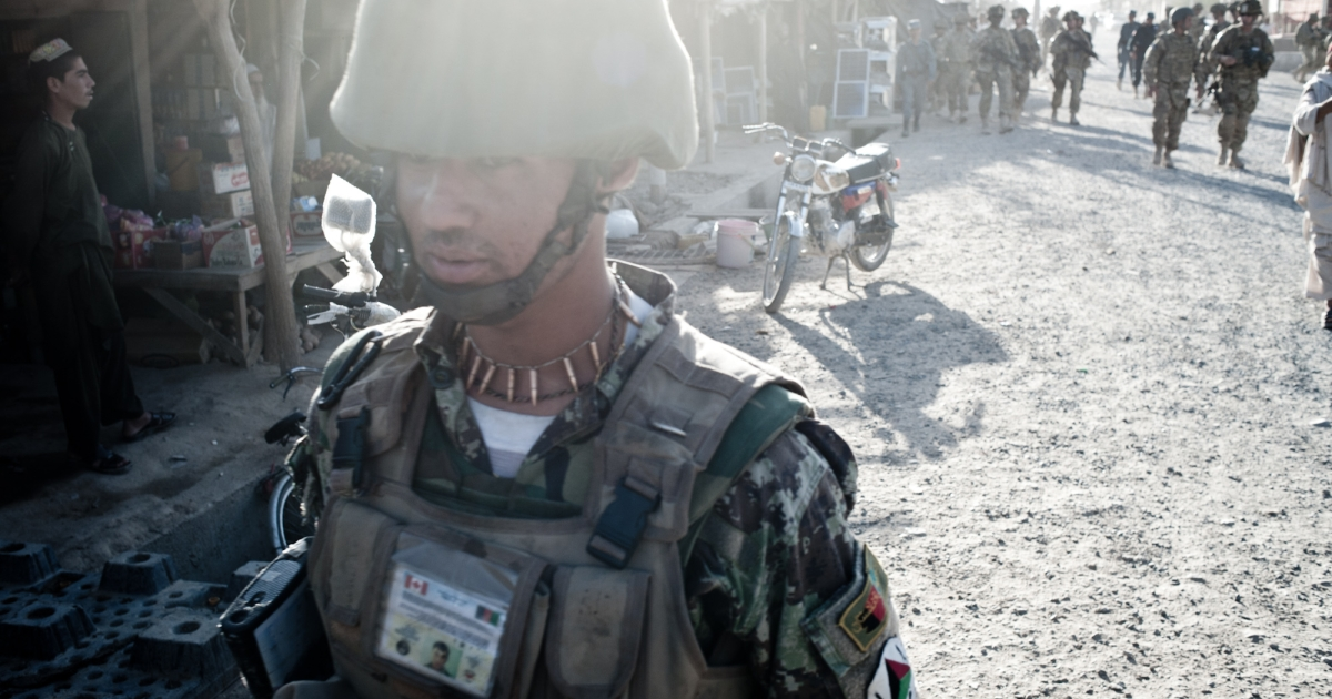 An Afghan soldier patrols through the Hutal bazaar, the largest outdoor market west of Kandahar City.</p>