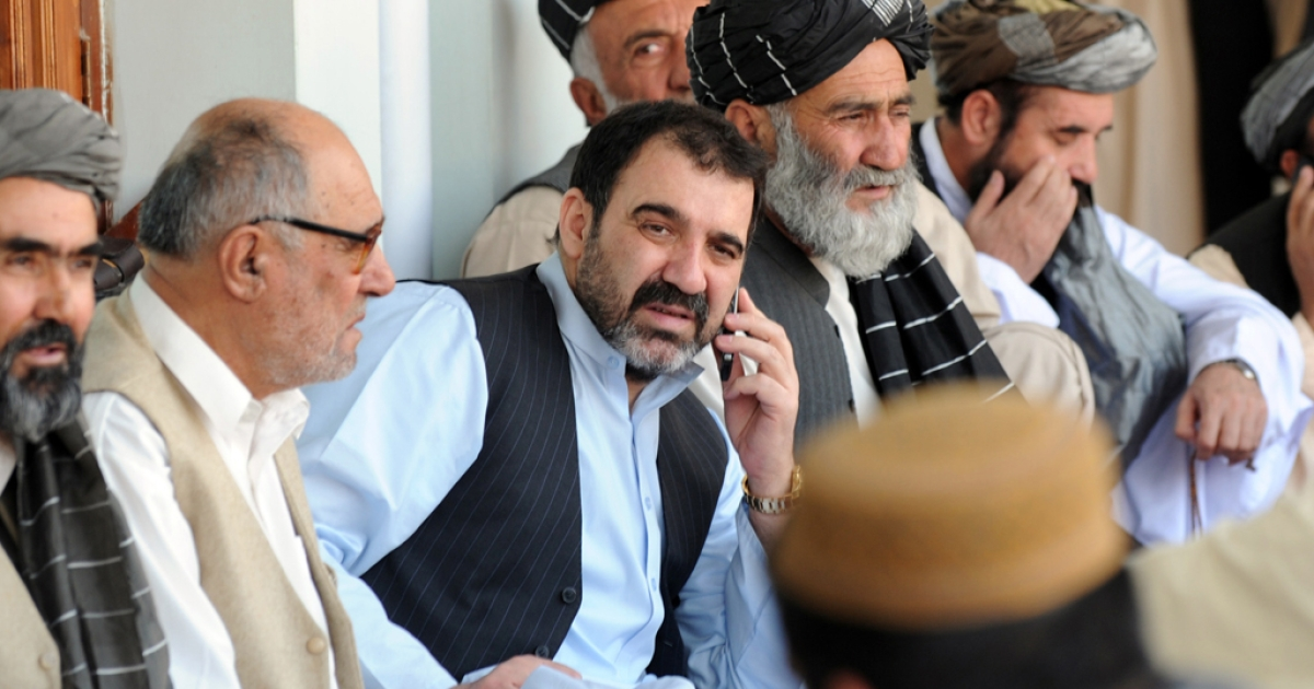 Ahmed Wali Karzai (C) talks on the phone as he sits with supporters celebrating the re-election victory of his brother President Hamid Karzai in Kandahar on November 3, 2009.</p>