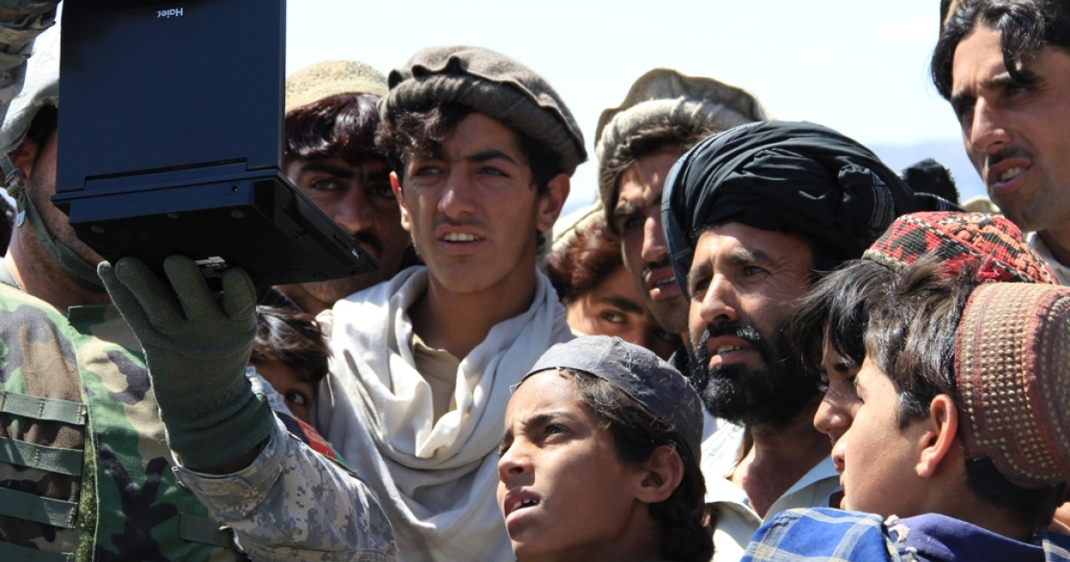 Afghan villagers watch a U.S. propaganda film on a portable DVD player that attempts to explain why the U.S. military is in Afghanistan.</p>