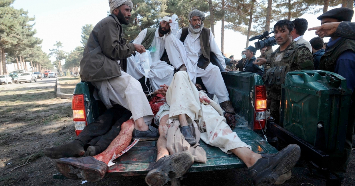 Afghan men sit on the back of a police vehicle laden with the victims of a suicide bomb attack in Herat Province on April 10, 2012. At least nine people were killed when two suicide bombers rammed their vehicle into a local government compound near Afghanistan's western city of Herat on on April 10, police and witnesses said.</p>