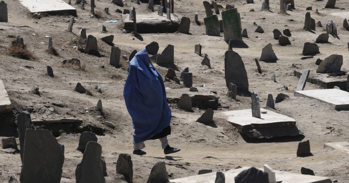 An Afghan woman walks in a Muslim cemetery in Kabul on March 9, 2011.</p>